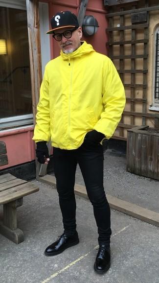 Comment porter: coupe-vent jaune, jean skinny noir, chaussures derby en cuir noires, casquette de base-ball imprimée noire