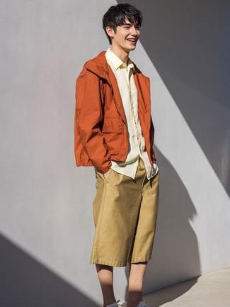 Comment porter: coupe-vent orange, chemise à manches longues en lin jaune, short marron clair, baskets basses blanches