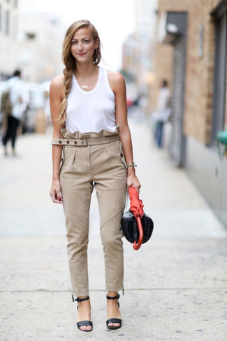 La polyvalence d'un débardeur blanc et d'un pantalon slim beige en fait des pièces de valeur sûre. Une paire de des sandales à talons en cuir noires apportera une esthétique classique à l'ensemble.