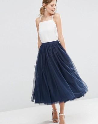 Comment porter: débardeur en soie blanc, jupe évasée de tulle bleu marine, sandales à talons en cuir argentées