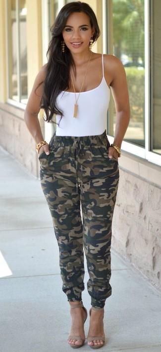 """Si tu es une fille plutôt """"jean t-shirt"""", tu vas aimer le combo simple d'un débardeur blanc et d'un pantalon de jogging olive. D'une humeur audacieuse? Complète ta tenue avec une paire de des sandales à talons en cuir grises."""
