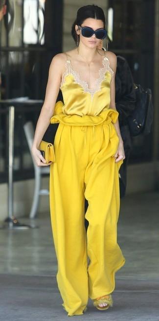 Comment porter un pantalon large jaune: Essaie d'harmoniser un débardeur en soie jaune avec un pantalon large jaune pour obtenir un look relax mais stylé. Tu veux y aller doucement avec les chaussures? Choisis une paire de des sandales plates en fourrure jaunes pour la journée.