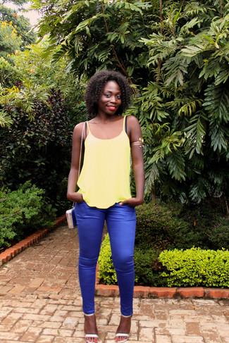 Comment porter: débardeur jaune, pantalon slim bleu, sandales à talons en cuir argentées, sac bandoulière en cuir bleu