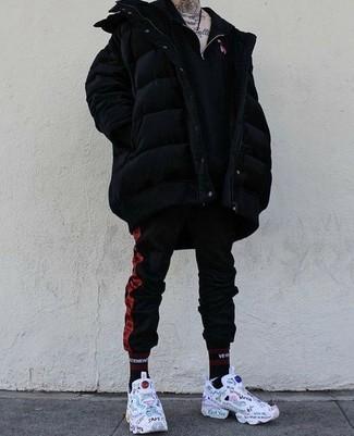 Comment porter: doudoune longue noire, pull à col à fermeture éclair noir, pantalon de jogging à rayures verticales rouge et noir, chaussures de sport imprimées blanches