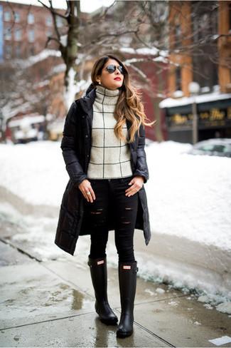 Comment porter: doudoune longue noire, pull à col roulé en laine beige, jean skinny déchiré noir, bottes de pluie noires