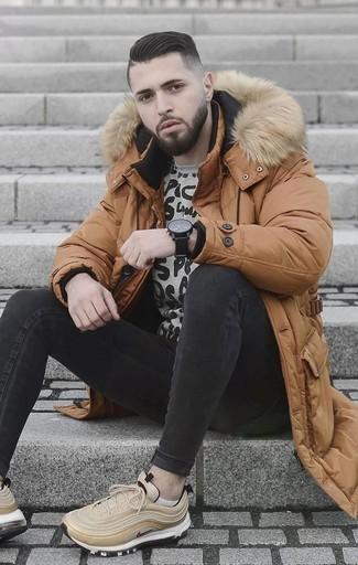 Comment porter: doudoune longue tabac, sweat-shirt imprimé gris, jean skinny noir, chaussures de sport beiges
