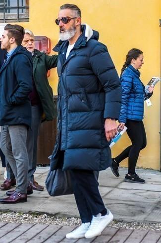 Comment porter un pantalon chino bleu marine: Essaie de marier une doudoune longue bleu marine avec un pantalon chino bleu marine pour une tenue confortable aussi composée avec goût. Mélange les styles en portant une paire de des baskets basses blanches.