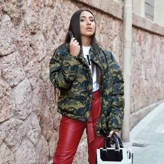 Comment porter: doudoune camouflage olive, t-shirt à col rond imprimé blanc et noir, pantalon carotte en cuir rouge, sac fourre-tout en cuir blanc et noir