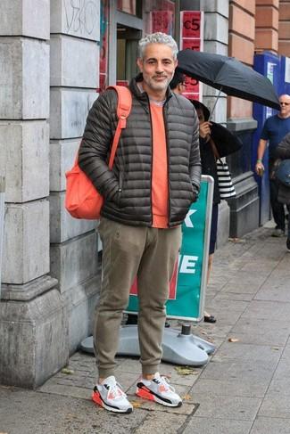 Comment porter: doudoune gris foncé, pull à col rond orange, t-shirt à col rond gris, pantalon de jogging olive