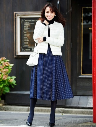 Comment porter: doudoune blanche, pull à col roulé noir, jupe mi-longue á pois bleu marine, escarpins en cuir noirs