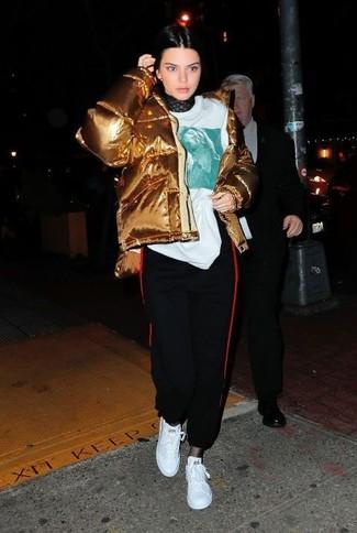 Comment porter: doudoune dorée, pull à col roulé en dentelle noir, t-shirt à col rond imprimé blanc, pantalon de jogging noir