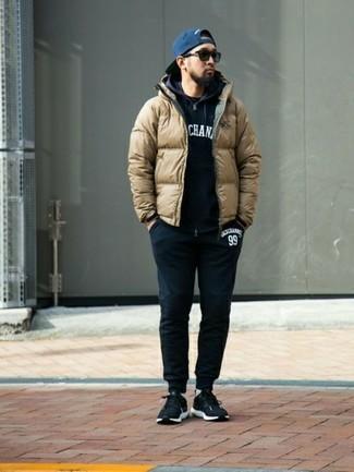 Comment porter: doudoune marron clair, sweat à capuche imprimé noir et blanc, t-shirt à col rond noir, pantalon de jogging noir