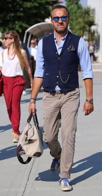 Comment porter: gilet bleu marine, chemise à manches longues en chambray bleu clair, pantalon chino beige, baskets basses en daim beiges