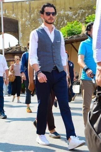 Comment porter une ceinture en cuir tressée noire: Pense à marier un gilet bleu avec une ceinture en cuir tressée noire pour une tenue idéale le week-end. Complète ce look avec une paire de des baskets basses en toile blanc et vert.