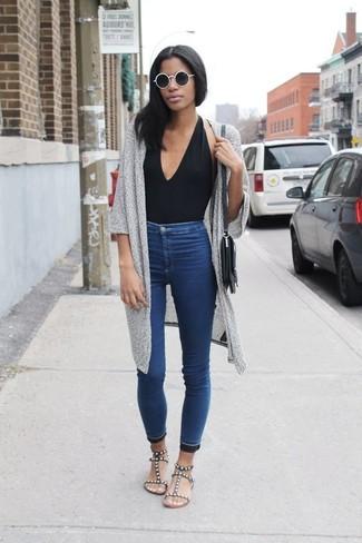 Comment porter: gilet en tricot gris, débardeur noir, jean skinny bleu, sandales plates en cuir à clous noires