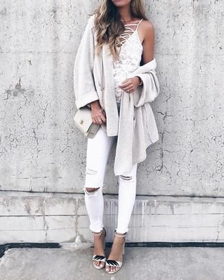Comment porter: gilet en tricot beige, débardeur en dentelle blanc, jean skinny déchiré blanc, sandales à talons en cuir blanches