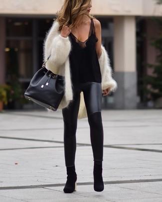 Comment porter des leggings en cuir noirs: Pense à marier un gilet duveteux blanc avec des leggings en cuir noirs pour une tenue relax mais stylée. Une paire de des bottines en daim noires est une option avisé pour complèter cette tenue.