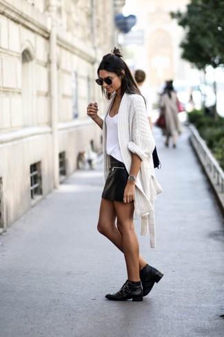 Comment porter: gilet en tricot blanc, débardeur blanc, minijupe en cuir noire, bottines en cuir à clous noires
