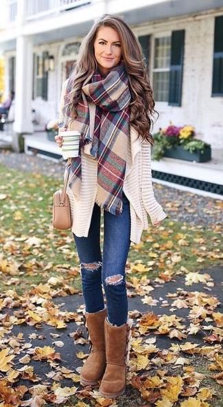 Comment porter: gilet en tricot beige, jean skinny déchiré bleu marine, bottes ugg marron, sac bandoulière en cuir beige