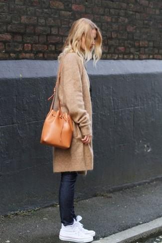 Comment porter: gilet en tricot marron clair, jean skinny bleu marine, baskets montantes blanches, sac bourse en cuir marron clair