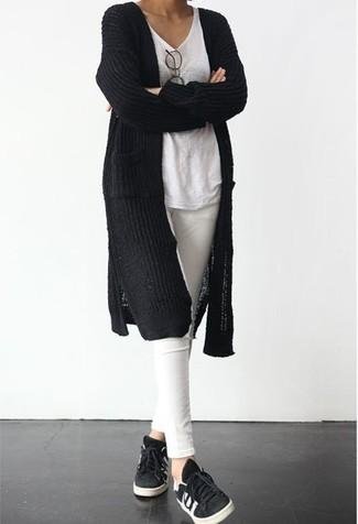 Comment porter: gilet en tricot noir, t-shirt à col en v blanc, jean skinny blanc, baskets basses noires