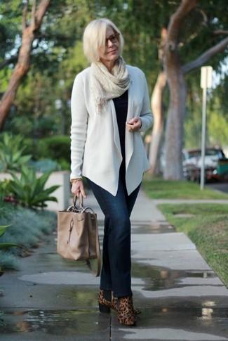 Comment porter: gilet blanc, pull à col rond noir, jean bleu marine, bottines en daim imprimées léopard marron