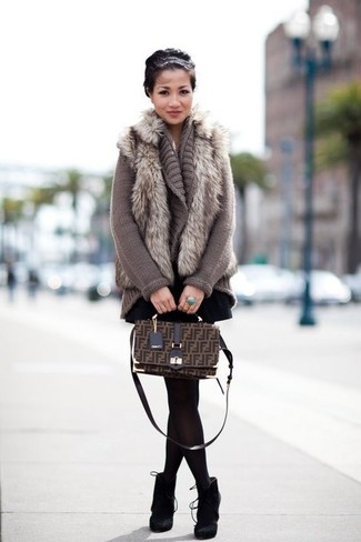 Comment porter: gilet sans manches en fourrure gris, gilet en tricot gris, jupe patineuse noire, bottines en daim noires