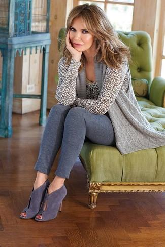 Comment porter: gilet sans manches en tricot gris, pull à col rond imprimé léopard gris, leggings gris, bottines en daim découpées grises