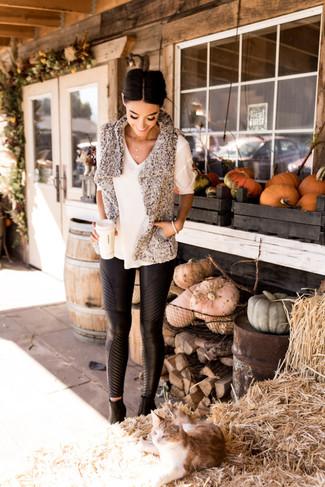 Comment porter: gilet sans manches en fourrure gris, pull à manches courtes blanc, pantalon slim en cuir noir, bottines en cuir noires