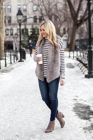 Comment porter: gilet sans manches en fourrure gris, pull à col roulé à rayures horizontales blanc et noir, jean skinny bleu marine, bottines en daim grises