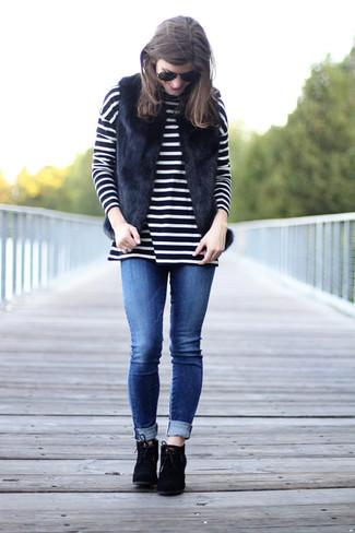 Comment porter: gilet sans manches en fourrure noir, pull à col roulé à rayures horizontales noir et blanc, jean skinny bleu, bottines à lacets en daim noires