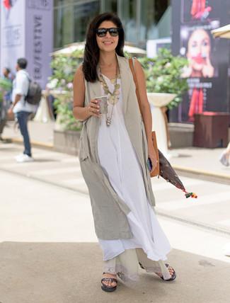Comment porter: gilet sans manches beige, robe longue en lin blanche, sandales plates en cuir noires, sac bourse en cuir marron clair