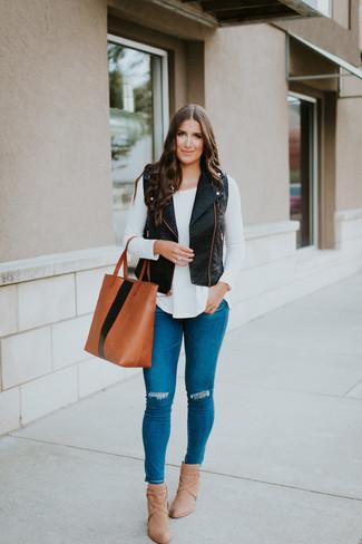 Comment porter: gilet sans manches en cuir noir, t-shirt à manche longue blanc, jean skinny déchiré bleu, bottines en cuir marron clair