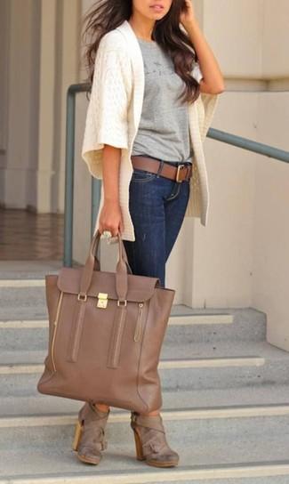Comment porter: gilet en tricot blanc, t-shirt à col rond imprimé gris, jean skinny bleu marine, bottines en cuir marron