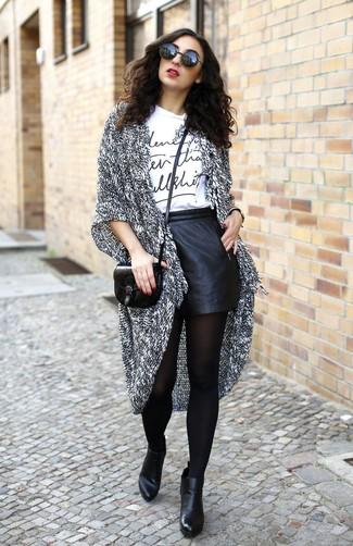 Comment porter des collants noirs quand il fait chaud: Choisis un gilet en tricot gris et des collants noirs pour une tenue relax mais stylée. Cette tenue se complète parfaitement avec une paire de des bottines en cuir noires.