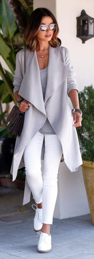 Comment porter: gilet gris, t-shirt à manche longue gris, jean skinny blanc, chaussures richelieu en cuir blanches