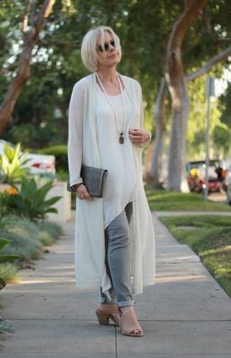 Comment porter une pochette en daim grise: Choisis pour le confort dans un gilet beige et une pochette en daim grise. Fais d'une paire de des mules en cuir marron clair ton choix de souliers pour afficher ton expertise vestimentaire.