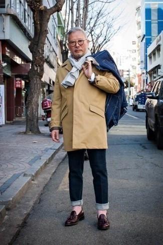 Tendances mode hommes: Pour une tenue de tous les jours pleine de caractère et de personnalité essaie de marier un imperméable marron clair avec un jean bleu marine. Termine ce look avec une paire de des mocassins à pampilles en cuir bordeaux pour afficher ton expertise vestimentaire.