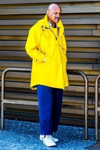 Comment porter des baskets basses en toile blanches: Porte un imperméable jaune et un pantalon chino bleu pour une tenue confortable aussi composée avec goût. Cette tenue est parfait avec une paire de des baskets basses en toile blanches.