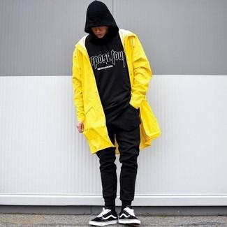 Comment porter: imperméable jaune, sweat à capuche imprimé noir et blanc, pantalon de jogging noir, baskets basses en daim noires