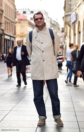 Comment porter: imperméable beige, jean bleu marine, bottines chukka en daim olive, sac à dos en cuir noir