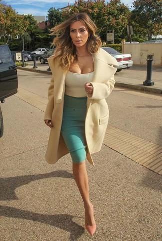 Tenue de Kim Kardashian: Manteau beige, Débardeur beige, Jupe crayon verte, Escarpins en cuir roses