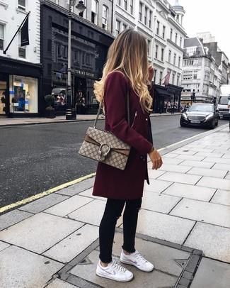 Comment porter: manteau bordeaux, jean skinny noir, baskets basses en cuir blanches, cartable en toile imprimé beige