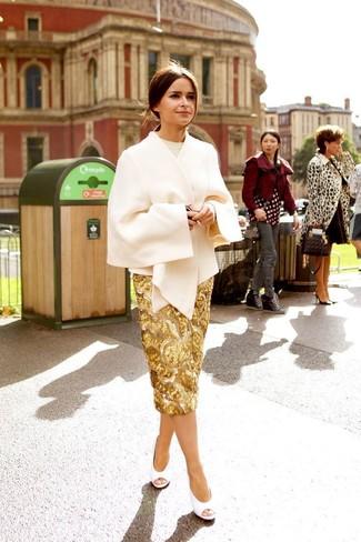Opte pour un manteau cape beige avec une jupe crayon pailletée dorée pour prendre un verre après le travail. Cette tenue se complète parfaitement avec une paire de des escarpins en cuir découpés blancs.