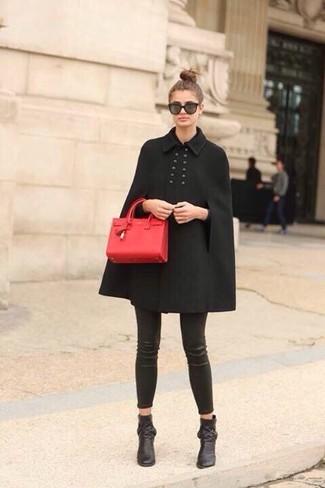 Comment porter: manteau cape noir, leggings en cuir noirs, bottines en cuir noires, cartable en cuir rouge