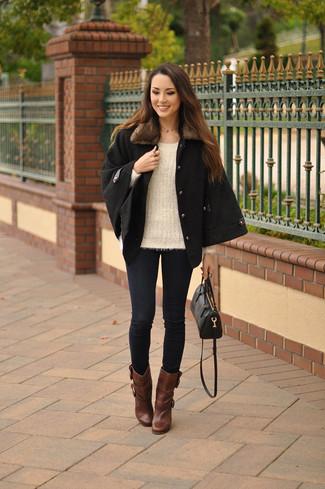 Comment porter: manteau cape noir, pull à col rond beige, jean skinny bleu marine, bottines en cuir marron
