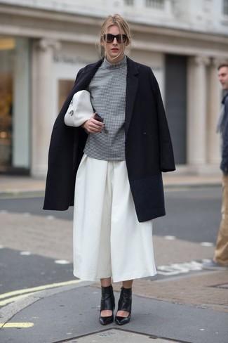 Tendances mode femmes: Porte un manteau noir et une jupe-culotte blanche pour obtenir un look relax mais stylé. Cette tenue est parfait avec une paire de des bottines en cuir découpées noires.