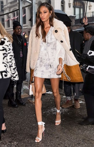 Comment porter: manteau de fourrure beige, robe droite à fleurs blanche, sandales à talons en cuir blanches, cartable en cuir marron clair
