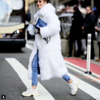 Comment porter: manteau de fourrure blanc, jean skinny bleu, chaussures de sport blanches, sac bandoulière en cuir bleu