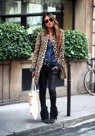 Comment porter: manteau de fourrure imprimé léopard marron clair, chemise en jean bleue, jean skinny en cuir noir, bottines en daim à franges noires